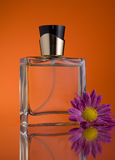 Botella de perfume con una flor Fotos de archivo