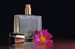 Botella de perfume con una flor Imagen de archivo libre de regalías