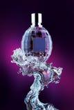 Botella de perfume en chapoteo del agua foto de archivo libre de regalías