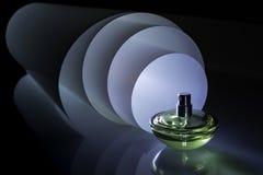 Botella de perfume en el fondo de un rollo luminoso espiral Idea fotos de archivo