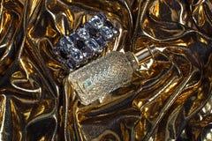 Botella de perfume en fondo brillante del oro Fotos de archivo libres de regalías