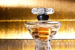 Botella de perfume en fondo del oro Imágenes de archivo libres de regalías