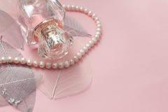 Botella de perfume en un fondo rosado Fotos de archivo libres de regalías