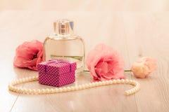 Botella de perfume de las mujeres con la caja y las flores de regalo en fondo rosado imagen de archivo