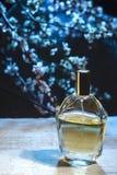 Botella de perfume de los men's en un fondo floral oscuro imagenes de archivo