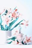Botella de perfume lujosa con las flores en el fondo blanco Concepto femenino de la belleza Fotos de archivo