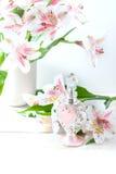 Botella de perfume lujosa con las flores en el fondo blanco Concepto femenino de la belleza Fotografía de archivo libre de regalías