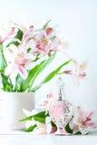 Botella de perfume lujosa con las flores en el fondo blanco Concepto femenino de la belleza Foto de archivo libre de regalías