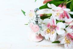 Botella de perfume lujosa con las flores en el fondo blanco Concepto femenino de la belleza Fotos de archivo libres de regalías