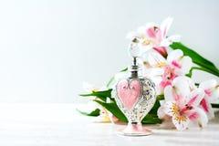 Botella de perfume lujosa con las flores en el fondo blanco Concepto femenino de la belleza Imagen de archivo