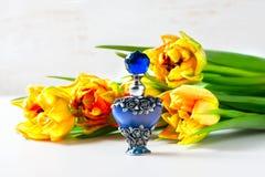 Botella de perfume lujosa con las flores en el fondo blanco Concepto femenino de la belleza Imagenes de archivo