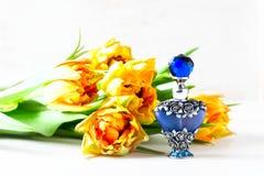 Botella de perfume lujosa con las flores en el fondo blanco Concepto femenino de la belleza Imagen de archivo libre de regalías