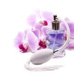 Botella de perfume, orquídeas rosadas en el fondo blanco. Imagen de archivo