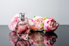 Botella de perfume rosada con las flores en fondo blanco y negro Perfumería, cosméticos, colección de la fragancia imágenes de archivo libres de regalías