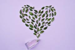 Botella de perfume y de hojas verdes dispuestos en forma del corazón sobre el fondo violeta Primavera o fragancia apacible del ve imágenes de archivo libres de regalías