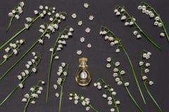 Botella de perfume y de lirios de las flores del valle en fondo negro Perfumería, fragancia, concepto cosmético Primavera o veran imagen de archivo