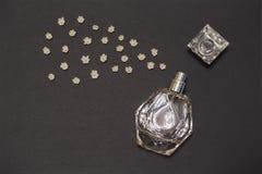 Botella de perfume y de lirios de los brotes de flor del valle en fondo negro Perfumería, fragancia, concepto cosmético Primavera imágenes de archivo libres de regalías