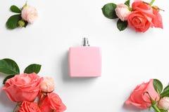 Botella de perfume y de rosas en el fondo blanco foto de archivo libre de regalías