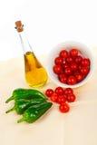 Botella de petróleo, cereza roja de los tomates y pimienta verde Imagenes de archivo