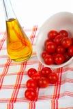 Botella de petróleo y cereza de los tomates Fotografía de archivo