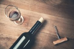 Botella de sacacorchos y de vidrio del vino en el fondo de madera foto de archivo