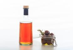 Botella de vinagre y de aceitunas en el fondo blanco fotografía de archivo