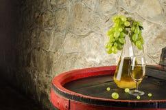 Botella de vino blanco, de copa de vino y de uvas blancas en barril Fotos de archivo libres de regalías