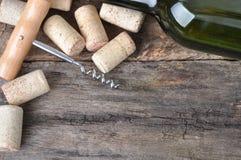 Botella de vino blanco, de sacacorchos y de corchos en la tabla de madera Imagenes de archivo