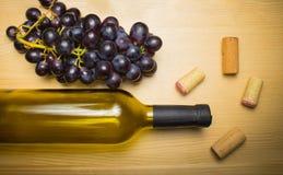Botella de vino con el sacacorchos en fondo de madera Imagenes de archivo