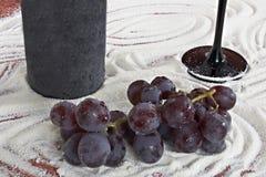 Botella de vino con un cubilete y un manojo de uvas Foto de archivo
