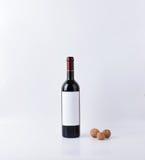 Botella de vino de la maqueta con tres nueces aisladas Fotografía de archivo