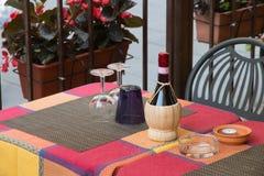 Botella de vino de mimbre en una tabla toscana del restaurante Fotografía de archivo