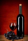 Botella de vino, de vidrio y de uvas sobre rojo imagen de archivo libre de regalías