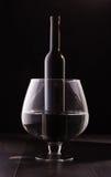 Botella de vino en la copa de vino grande aislada Imagen de archivo