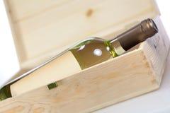Botella de vino en primer de la caja de madera en el backgound blanco imagen de archivo
