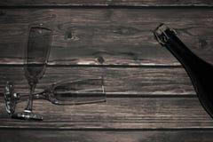 Botella de vino espumoso y de vidrios en los tableros de madera Imagen de archivo libre de regalías