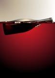 Botella de vino que flota en el vino rojo Imagenes de archivo