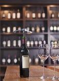 Botella de vino rojo con dos copas de vino y sacacorchos Foto de archivo