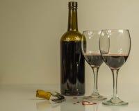 Botella de vino rojo con dos vidrios y corazones Imagenes de archivo