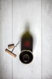 Botella de vino rojo con el corcho en la tabla de madera blanca Imagen de archivo