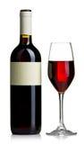 Botella de vino rojo con el vidrio claro con el vino rojo aislado Imagen de archivo libre de regalías
