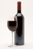 Botella de vino rojo con la copa llenada en frente Imagen de archivo
