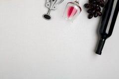 Botella de vino rojo con los vidrios en la maqueta blanca de la opinión superior del fondo Imagen de archivo