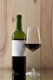 Botella de vino rojo con un vidrio brillante en un fondo de madera en un soporte de cristal Imagen de archivo