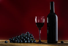 Botella de vino rojo, de copas de vino y de uva Foto de archivo