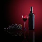 Botella de vino rojo, de copas de vino y de uvas Imagenes de archivo