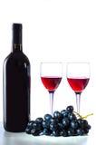 Botella de vino rojo, de copas de vino y de uvas Foto de archivo libre de regalías