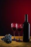 Botella de vino rojo, de copas de vino y de uvas en un backgroun rojo Fotos de archivo libres de regalías
