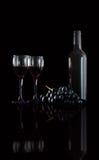 Botella de vino rojo, de dos copas de vino y de uvas en un backg negro Fotografía de archivo