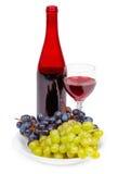 Botella de vino rojo, de vidrio y de uvas Foto de archivo